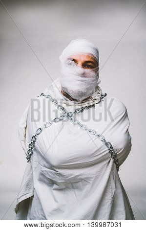Angry man with his head and face bandaged - isolated on white.