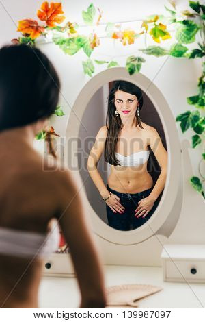 Sexy adorable young woman posing in the mirror smiling