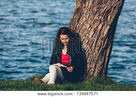 Charming girl relaxing in the park while read book while holding her back on a tree