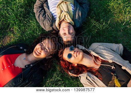 Closeup of three happy woman lying on the grass in a sunny day