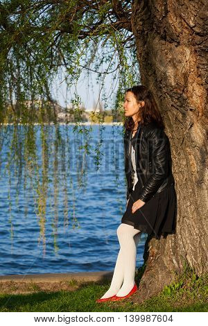 Profile of a serene dreamy woman standing near a tree in a park and looking away