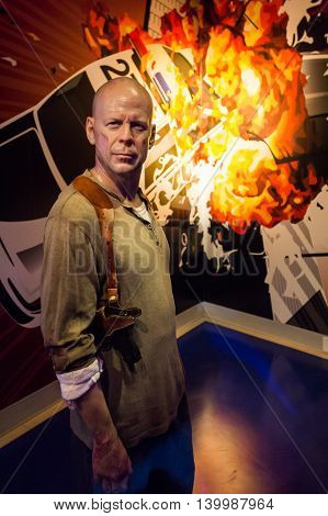 Los Angeles CA USA - July 6 2013: Madame Tussaud's Hollywood figures - Bruce Willis. On background exploding police vehicle.