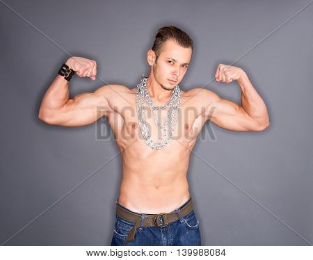 Tense angry man with chains around neck showing biceps