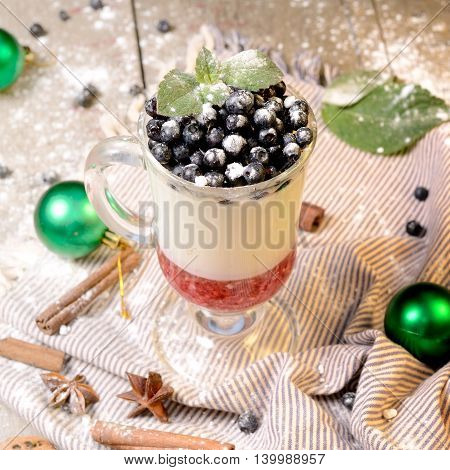 Delicious parfait dessert with bilberry berries, milk souffle and jello layers. Frozen treat in a glass on a rustic wooden background