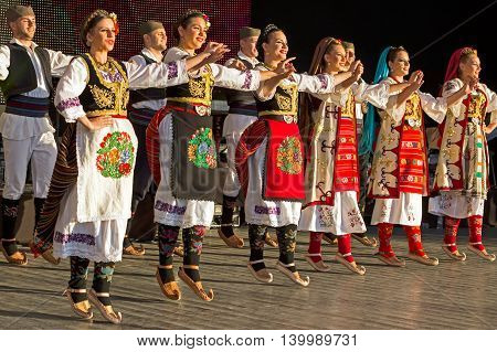 """ROMANIA TIMISOARA - JULY 7 2016: Young Serbian dancers in traditional costume perform folk dance during """" International Festival of hearts """" organized by the City Hall Timisoara."""