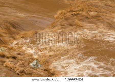 Closeup of rapid flow of brown water in the muddy river during rainy season, slow motion photo