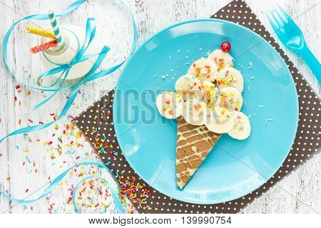 Ice cream cone pancake with banana and milk for creative kid breakfast. Fun food art idea for children food top view