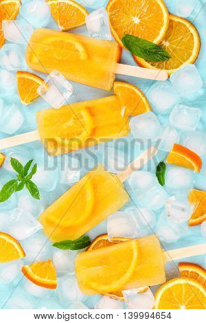 Fruit Orange Ice Lolly, Ice Cubes And Slices Of Orange On Light Blue Background. Top View.