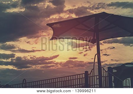 Big Umbrella Against A Cloudy Sunset At The Play Ground