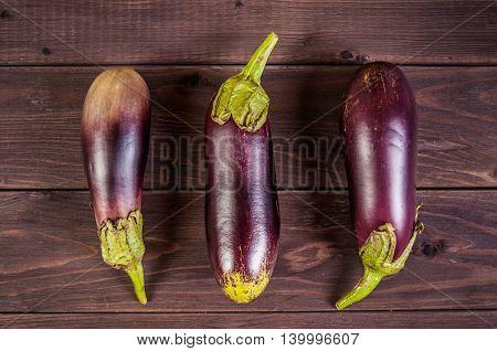 Fresh organic eggplants on a wooden background