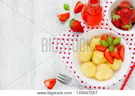 Cottage cheese dumplings with fresh strawberries on white background top view blank space for text