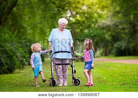 Happy senior lady with a walker holding hands of little boy and girl. Grandmother with grand children enjoy a walk in summer park. Kids supporting disabled grandparent.