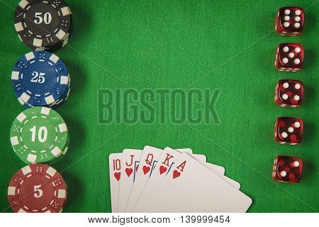 Gambling chips, red dice and flush royal on green card table background
