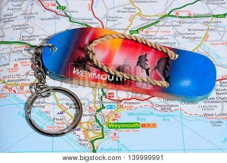 WEYMOUTH, UNITED KINGDOM - JULY 24, 2016 - Sandal Weymouth key ring on a map Weymouth Dorset England UK Western Europe, July 24, 2016.