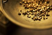 Trade and exchange. Weighing a gold nugget on a old brass scale dish.for trading. Shallow depth of filed. poster