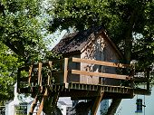 Beautiful creative handmade tree house for kids in backyard of a house poster