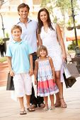 Young Family Enjoying Shopping Trip Together poster