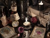 Close up of the tarot cards, warlock book, vintage bottles, books and candles. Halloween concept, black magic ritual or spell with occult and esoteric symbols, divination rite poster
