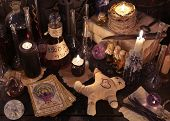 Mystic still life with voodoo doll, the tarot cards, book, evil candles and witchcraft objects. Halloween concept, black magic ritual or spell with occult and esoteric symbols, divination rite poster