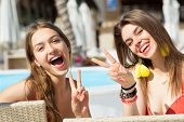 Two cool trendy funny girls in swimwear at beach chairs poster