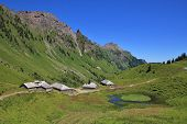 Rural scene in Glarus Canton. Huts and sheds on the Lachenalp. Pond and mountains. poster