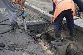 Road Paving Construction. Workers laying stone mastic asphalt during street repairing works. Worker making asphalt with coated chippings. Drainage repair installation of manhole poster