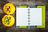 Top view. Garcinia cambogia fresh fruit on wood background with book. Garcinia atroviridis is a spice plants and high vitamin C and hydroxy citric acids (HCA) for diet and good health. poster