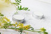 Facial herbal cosmetic cream in containers, fresh aromatic meadow herbs, sea salt scattered on white board. Chemical-free moisturizers. poster