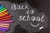 "Back to school background with colorful felt tip pens and title ""Back to school"" written by white chalk on the black school chalkboard poster"