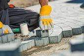 Brock Paving Closeup Photo. Construction Worker Paving Brick Pathway. poster