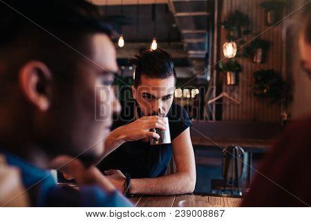 Happy Arabian Young Men Hanging In Loft Cafe. Friends Talking In Lounge Bar By The Window Drinking T