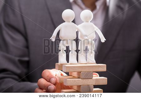 Two Human Figures Standing On Top Of Stacked Wooden Blocks Being Supported By Businessperson