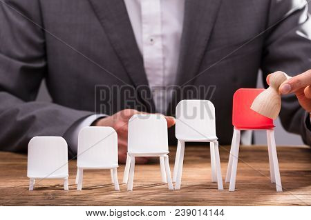 Businessperson Placing Pawn On Red Chair