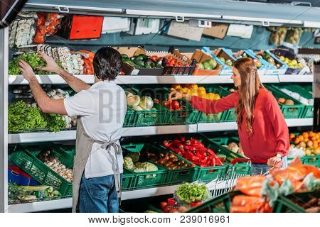 Side View Of Shop Assistant In Apron And Female Shopper In Hypermarket