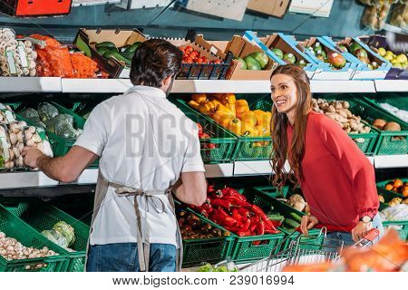 Back View Of Shop Assistant In Apron And Female Shopper In Hypermarket