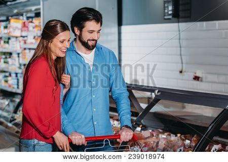 Happy Couple With Shopping Cart Shopping Together In Supermarket