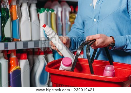 Partial View Of Shopper Putting Detergent Into Shopping Basket In Supermarket