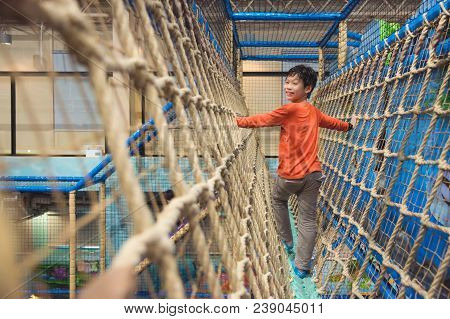 Young Asian Boy Climbing Rope At Indoors Playground