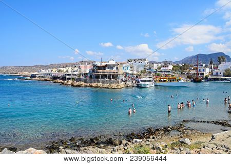 Sissi, Greece - September 14, 2016 - Tourists In The Sea Along The Rocky Shoreline With Views Of The