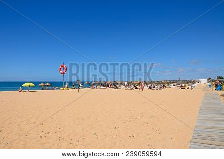 Vilamoura, Portugal - June 6, 2017 - View Along The Sandy Beach With Tourists Enjoying The Setting,