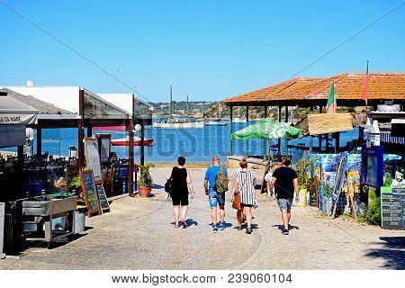 Alvor, Portugal - June 7, 2017 - Tourists Walking Along A Restaurant Lined Street With Views Towards