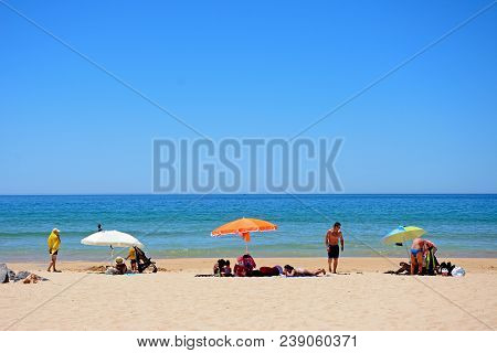 Portimao, Portugal - June 7, 2017 - Tourists Relaxing On The Beach With Views Out Over The Ocean, Po