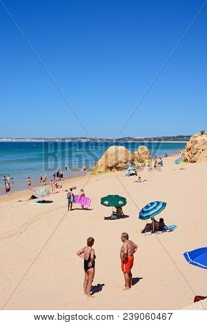 Portimao, Portugal - June 7, 2017 - Tourists Relaxing On The Beach With Large Rocks And Views Across