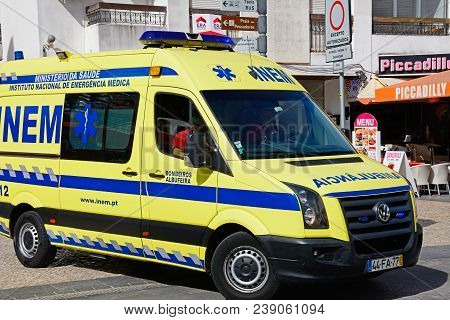 Albufeira, Portugal - June 10, 2017 - Portuguese Yellow And Blue Ambulance Along 25 De Abril Street
