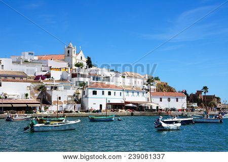 Ferragudo, Portugal - June 10, 2017 - View Of The White Town With Boats Moored In The Foreground, Fe