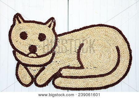 Wicker Cat Shaped Doormat Displayed Against A Wooden Door, Silves, Portugal, Europe.