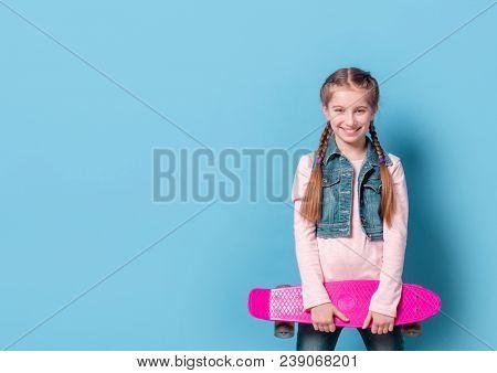 Teenage girl with pink skateboard
