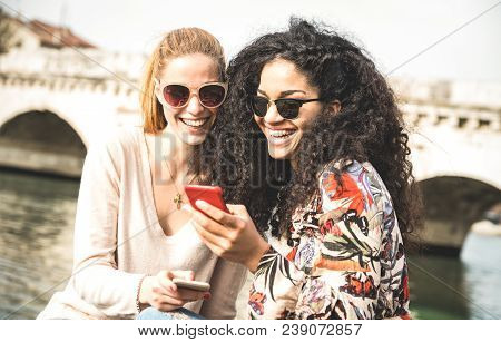 Happy Multiracial Girlfriends Having Fun Outddors With Mobile Smart Phone - Friendship Concept With