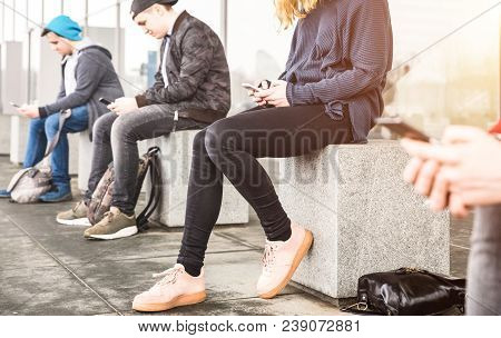 Group Of Friends Sitting And Using Smartphone At University College Backyard Break - Guys And Girls