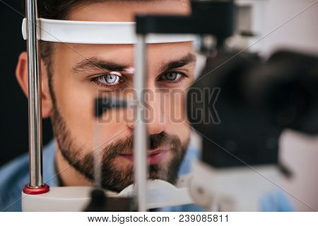 Handsome Young Man Is Checking The Eye Vision In Modern Ophthalmology Clinic. Patient In Ophthalmolo